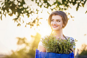 Young woman oustide in green nature gardening