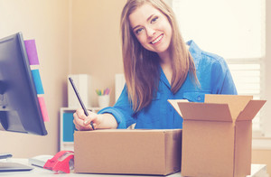 Young woman packing boxes to be shipped in her home office