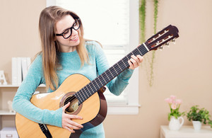 Young woman playing guitar in her house