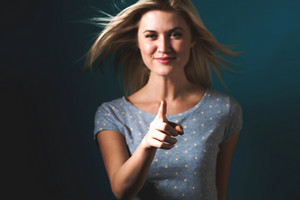 Young woman pointing something on a blue background
