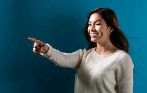 Young woman pointing something on a dark blue background
