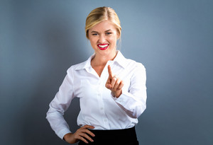 Young woman pointing something on a gray background
