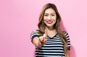 Young woman pointing something on a pink background