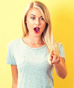 Young woman pointing something on a yellow background