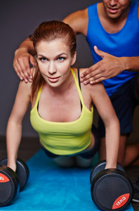 Young woman practicing weightlifting in gym with help of trainer