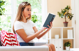 Young woman reading a book on a couch