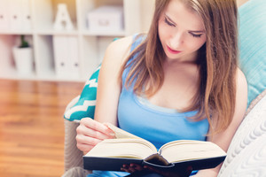 Young woman reading a book on her couch at home