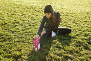 Young woman runner in warm clothes and headphones in autumn park make sport exercise
