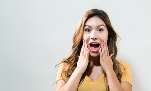 Young woman shouting on a off white background