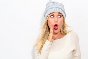 Young woman shouting on a white background