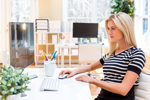 Young woman sitting at her desk in front of the computer