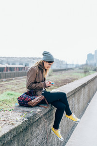 Young woman sitting in the city using smart phone hand hold - technology, social network, instant message concept