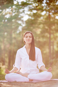 Young woman sitting in yoga pose with eyes closed and meditating