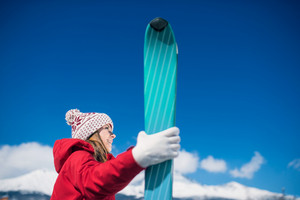 Young woman skiing outside in sunny winter mountains