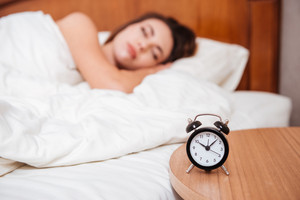 Young woman sleeping in bed in her bedroom, focus on alarm clock