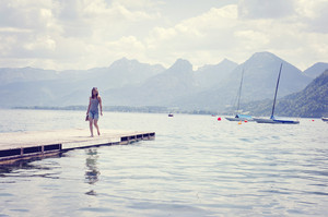 Young woman standing on the pier by the lake