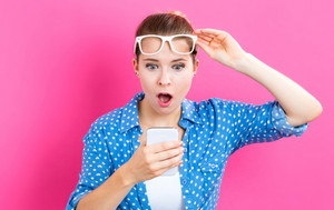 Young woman staring at her cellphone on a pink background
