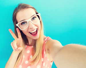 Young woman taking a selfie on blue background