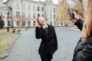 Young woman taking picture of her friend with university building on background