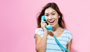 Young woman talking on old fashion phone on a pink background