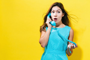 Young woman talking on old fashion phone on a yellow background