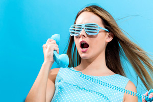Young woman talking on old fashioned phone