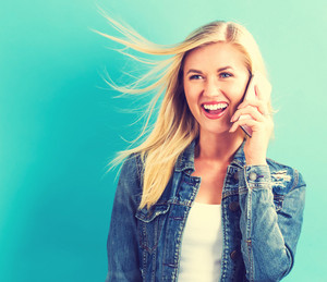 Young woman talking on the phone on a blue background