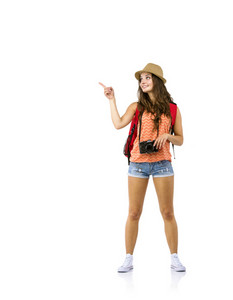 Young woman tourist with camera and backpack pointing somewhere, isolated on white
