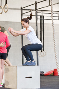 Young woman trains crossfit box jumps