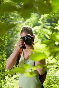 young woman trekking among trees and taking pictures with dslr camera. Vertical shape, front view, waist up