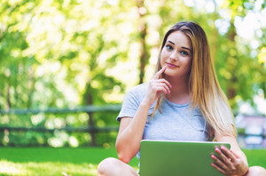 Young woman using her laptop outside on a summer day