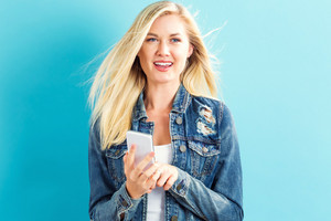 Young woman using her phone on a blue background