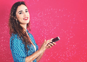 Young woman using her phone on a pink background with web concept