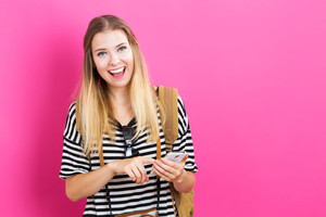 Young woman using her phone on a pink background