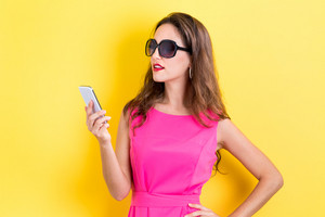 Young woman using her phone on a yellow background