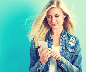 Young woman using her phone on blue background