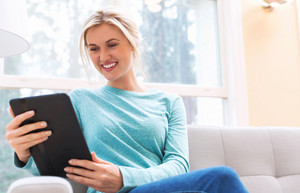 Young woman using her tablet computer at home