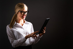 Young woman using her tablet on a black background