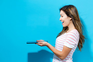 Young woman using her tablet on a blue background