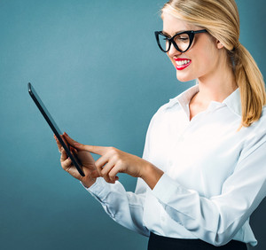 Young woman using her tablet on a blue gray background