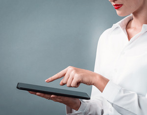 Young woman using her tablet on a gray background