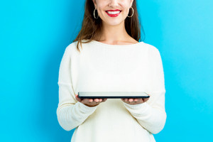 Young woman using her tablet on blue background