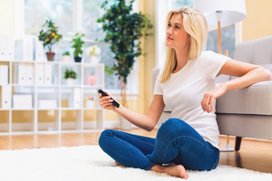 Young woman watching TV in the living room