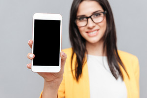 Young woman wearing eyeglasses and dressed in yellow jacket showing phone display to camera over grey background. Look at camera. Focus on phone.