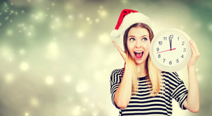 Young woman wearing Santa hat holding a clock showing nearly 12