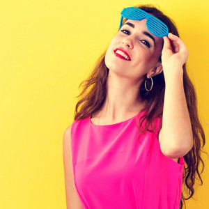 Young woman wearing shutter shades sunglasses on a yellow background
