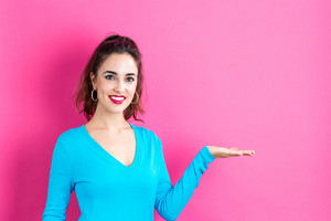 Young woman with a displaying hand gesture on a pink background
