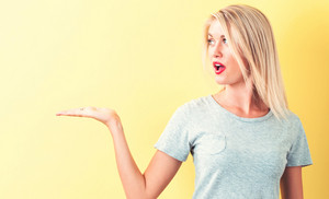 Young woman with a displaying hand gesture on a yellow background