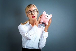 Young woman with a piggy bank on a gray background