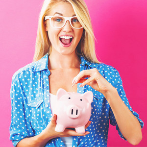 Young woman with a piggy bank on a pink background